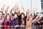 Fans reaching out over barrier Stock Photo - Premium Royalty-Free, Artist: Blend Images, Code: 635-05550172