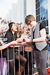 Celebrity signing autographs on red carpet Stock Photo - Premium Royalty-Free, Artist: Blend Images, Code: 635-05550191