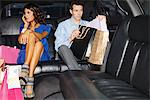 Couple with shopping bags in backseat of limo Stock Photo - Premium Royalty-Freenull, Code: 635-05550196