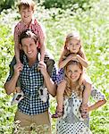 Parents holding children on shoulders in park Stock Photo - Premium Royalty-Freenull, Code: 635-05550207