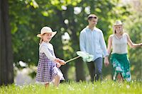 Girl playing with butterfly net in park Stock Photo - Premium Royalty-Freenull, Code: 635-05550228