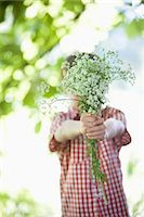 Boy offering bouquet of flowers Stock Photo - Premium Royalty-Freenull, Code: 635-05550232