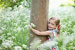 Girl hugging tree in field of flowers Stock Photo - Premium Royalty-Freenull, Code: 635-05550248