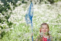 Girl playing with butterfly net in field of flowers Stock Photo - Premium Royalty-Freenull, Code: 635-05550252