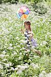 Girl playing with pinwheel in field of flowers Stock Photo - Premium Royalty-Free, Artist: Ikon Images, Code: 635-05550289