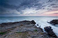 Rocks jutting into ocean under sky Stock Photo - Premium Royalty-Freenull, Code: 635-05550466