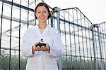 Scientist holding seedling outside greenhouse Stock Photo - Premium Royalty-Free, Artist: Blend Images, Code: 635-05550706