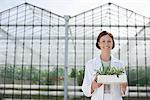 Scientist holding plants outside greenhouse Stock Photo - Premium Royalty-Free, Artist: Blend Images, Code: 635-05550724