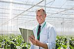 Businessman writing on clipboard in greenhouse Stock Photo - Premium Royalty-Freenull, Code: 635-05550755