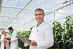 Scientist writing on clipboard in greenhouse Stock Photo - Premium Royalty-Freenull, Code: 635-05550762