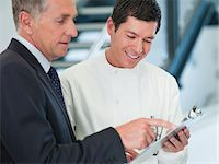 supervising - Businessman and scientist reading clipboard Stock Photo - Premium Royalty-Freenull, Code: 635-05550876