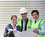 Business people examining blueprints on site Stock Photo - Premium Royalty-Free, Artist: Blend Images, Code: 635-05550937