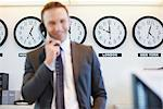 World clocks behind businessman in office Stock Photo - Premium Royalty-Free, Artist: Blend Images, Code: 635-05551047
