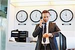 Businessman checking his watch in office Stock Photo - Premium Royalty-Free, Artist: Michael Mahovlich, Code: 635-05551066
