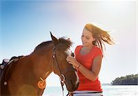 equestrian - Girl petting horse outdoors Stock Photo - Premium Royalty-Freenull, Code: 635-05551103
