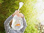 Girl holding goldfish in plastic bag Stock Photo - Premium Royalty-Freenull, Code: 635-05551125