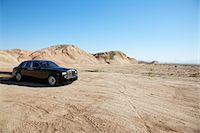 Rolls Royce car leaving trail of black oil behind on unpaved road Stock Photo - Premium Royalty-Freenull, Code: 693-05552682