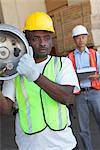 Warehouse worker carrying cylinder with manager in background Stock Photo - Premium Royalty-Free, Artist: iRepublic, Code: 693-05552717