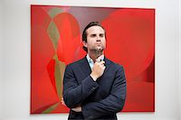 exhibition - Young adult man thinking in front of painting in art gallery Stock Photo - Premium Royalty-Freenull, Code: 693-05552745