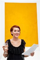 exhibition - Smiling young woman in front of yellow wall painting Stock Photo - Premium Royalty-Freenull, Code: 693-05552763