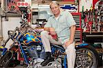 Senior man sitting on motorcycle in workshop Stock Photo - Premium Royalty-Free, Artist: Aurora Photos, Code: 693-05553151