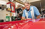 Portrait of smiling senior man cleaning hood of car Stock Photo - Premium Royalty-Free, Artist: Cusp and Flirt, Code: 693-05553154