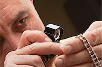 Close up of man looking at jewelry through magnifying glass Stock Photo - Premium Royalty-Freenull, Code: 693-05553383