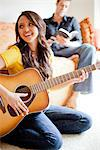 Young Woman Playing Guitar with Man Sitting Behind her Reading Stock Photo - Premium Rights-Managed, Artist: ableimages, Code: 822-05554319
