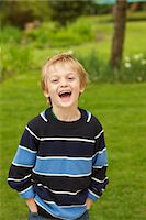 Boy Standing in a Garden with Hands in Pockets Stock Photo - Premium Rights-Managednull, Code: 822-05554419