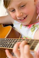 Young Girl Playing Guitar Stock Photo - Premium Rights-Managednull, Code: 822-05554436