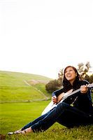 Young Woman Playing Guitar Outdoors Stock Photo - Premium Rights-Managednull, Code: 822-05554717