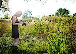 Woman Standing in a Meadow Holding Vintage Camera