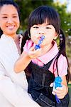 Girl Blowing Soap Bubbles in her Mother Arms Stock Photo - Premium Rights-Managed, Artist: ableimages, Code: 822-05554798