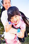 Girl Blowing Soap Bubbles in her Mother Arms Stock Photo - Premium Rights-Managed, Artist: ableimages, Code: 822-05554813