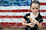 Girl Standing Behind Chain Link Fence Holding Chick