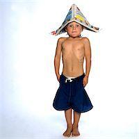 Boy Wearing Newspaper Hat Standing Straight and Stiff Stock Photo - Premium Rights-Managednull, Code: 822-05554834