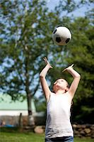 preteen girls stretching - Girl Throwing Football Above Head Stock Photo - Premium Rights-Managednull, Code: 822-05554897