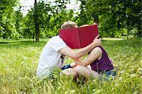 Teenagers hiding behind book in park Stock Photo - Premium Royalty-Freenull, Code: 649-05555613