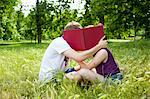 Teenagers hiding behind book in park Stock Photo - Premium Royalty-Free, Artist: Ikon Images, Code: 649-05555613