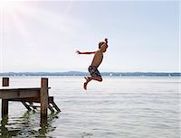 Boy jumping into lake from dock Stock Photo - Premium Royalty-Freenull, Code: 649-05556067