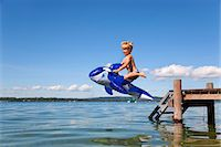 Boy jumping into lake with toy whale Stock Photo - Premium Royalty-Freenull, Code: 649-05556079