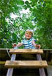 Smiling boy sitting in treehouse Stock Photo - Premium Royalty-Freenull, Code: 649-05556088