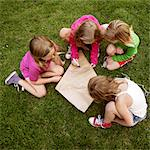Girls making a kite in grass Stock Photo - Premium Royalty-Free, Artist: Jason Friend, Code: 649-05556181