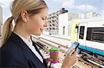 Businesswoman with coffee and smart phone in train station Stock Photo - Premium Royalty-Free, Artist: Robert Harding Images, Code: 614-05556687