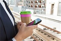 platform - Close up of woman with coffee and smart phone in train station Stock Photo - Premium Royalty-Freenull, Code: 614-05556688