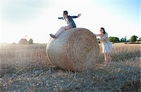 riding crop - Girls playing on hay bale in field Stock Photo - Premium Royalty-Freenull, Code: 649-05556619