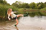 Teenage girl wading into the middle of a lake with over-flowing wellies Stock Photo - Premium Royalty-Freenull, Code: 614-05556990