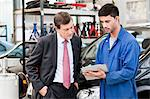 Businessman with car mechanics in repair garage Stock Photo - Premium Royalty-Free, Artist: CRed, Code: 614-05557266