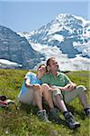 Couple Sitting on Mountain Side, Bernese Oberland, Switzerland