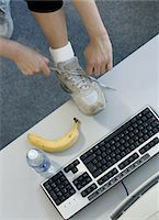 Woman tying shoe lace on desk by computer, elevated view Stock Photo - Premium Royalty-Freenull, Code: 6106-05562185